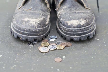 beggar: Coins next to beggar wearing old shoes, front shot with particular focus Stock Photo