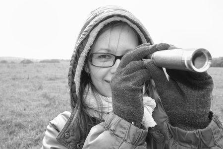 spy glass: Woman wearing hood looking through a spy glass, in black and white, concept of safety Stock Photo