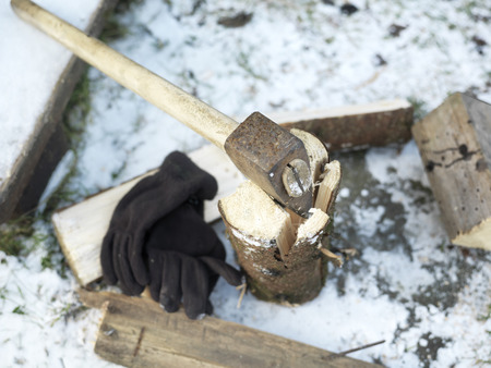 winter wood: Ax stuck in a piece of wood, snow and gloves in the background, shallow depth of field shot