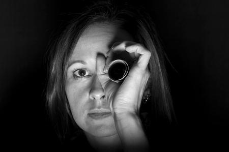 spy glass: Vigilant woman holding a bundle of dollars as a spy glass, black and white, studio shot Stock Photo