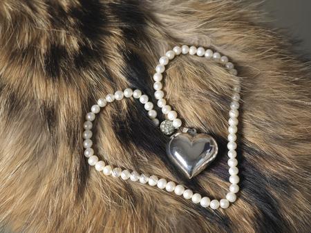 animal fur: Pearl beads in shape of heart laid on animal fur, closeup angled shot