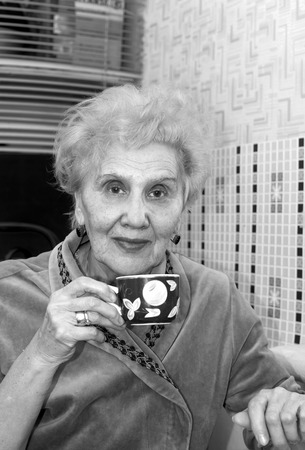 75s: Portrait of a senior female having tea or coffee in her kitchen, in black and white Stock Photo