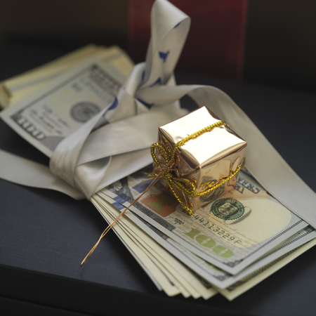 lavish: Banknotes as a gift with box wrapped in golden paper on top, concept of success, closeup angled shot