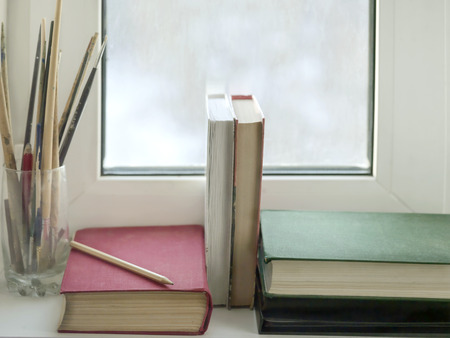 window sill: Books and artist brushes on a window sill, concept of free time