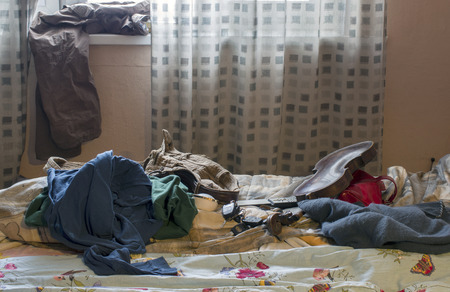 unmade: Unmade bed with ruffled blanket and various personal effects around in mess, indoor shot against the window