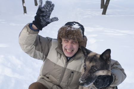 warm clothes: Man wearing fur hat and warm clothes waving his hand while holding a shepherd dog, selective focus outdoor shot
