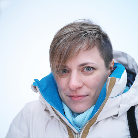 warm clothes: Portrait of a frozen woman wearing warm clothes  but no hat  posing outdoors, square soft focus  shot