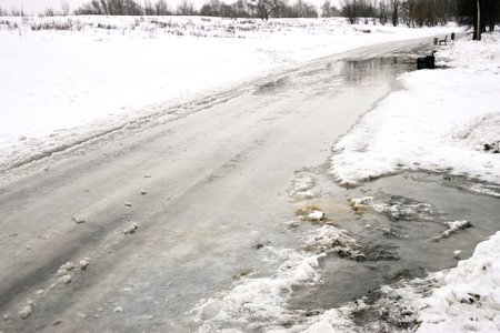 winter thaw: Late winter or early spring thaw, snow melting on a road in a park