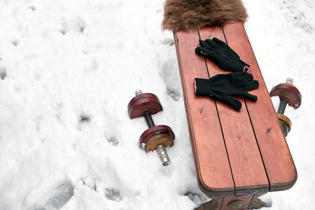 weightlifting gloves: Dumbbells lying on a snow under wooden bench, concept of physical activity, outdoor winter shot Stock Photo
