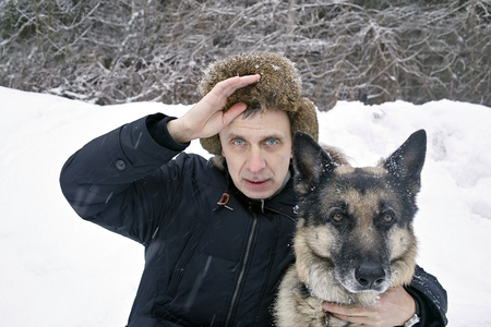 nasty: Man wearing warm winter clothes posing with shepherd dog in a nasty weather day