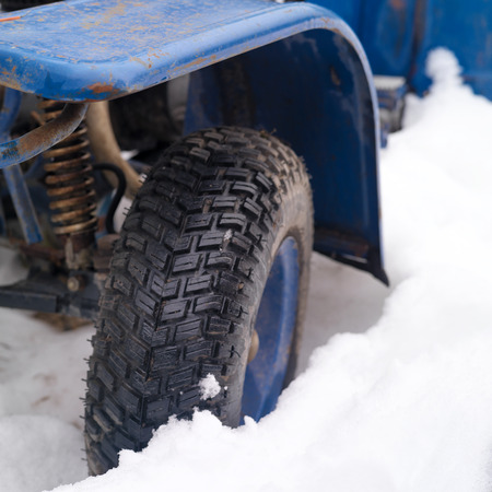 motorized: Wheel of motorized vehicle stuck in snow, selective focus closeup shot