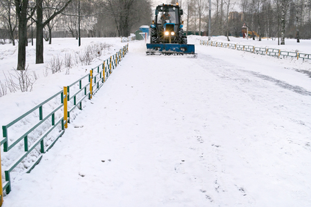 scraper: Front shot of a tractor removing snow with scraper blade, urban landscape in the blurred background