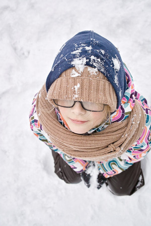 pulled over: Girl standing deep in snow with a hat pulled over her eyes, overhead vertical shot Stock Photo