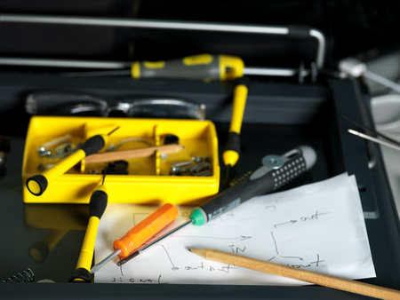 focus on the foreground: Screwdrivers and pencil above the hand drawn scheme, closeup shot with focus in the foreground
