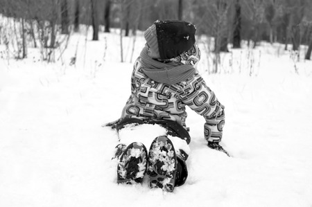 warm clothes: Little girl wearing warm clothes sitting on the snow, focus in the foreground, in black and white Stock Photo