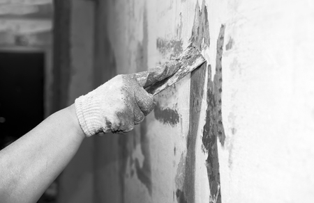 scrapers: Hand in protective glove cleaning the wall with scraper, concept of renovation Stock Photo