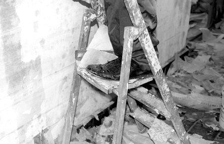 mess: Feet of worker standing on ladder, mess on the floor, in black and white