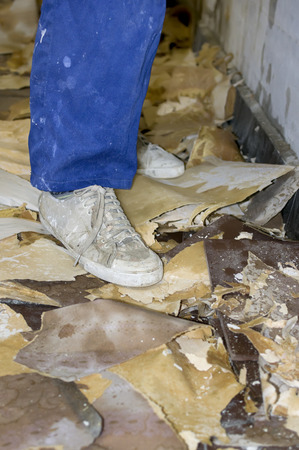 dirty feet: Worker feet wearing sport shoes and dirty trousers standing in a room under renovation, vertical indoor shot