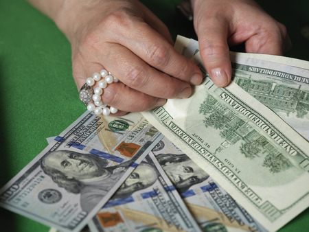 us dollars: Female hands wearing jewelry counting US dollars on a gambling table, closeup shot with selective focus