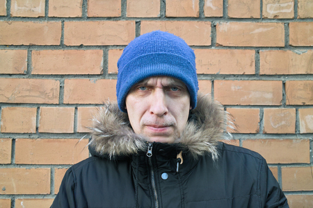 sullen: Man with a sullen look on his face posing next to a brick wall