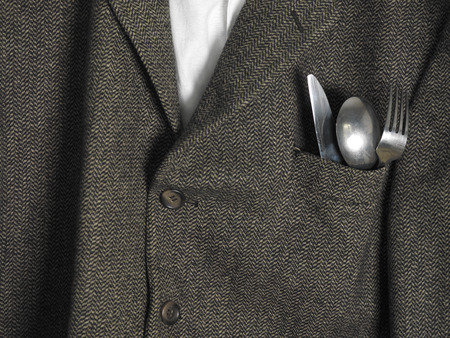 breast pocket: Coat of a man ready for dinner with cutlery sticking out of the pocket, concept of hunger Stock Photo