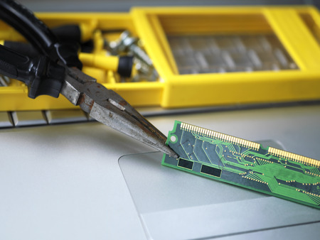 hardware repair: Macro shot with a shallow depth of field of pliers holding computer chip or board