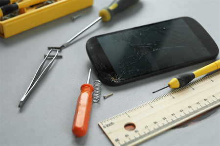 focus shot: Selective focus shot of the mobile phone with damaged screen, working tools laid around it on the table