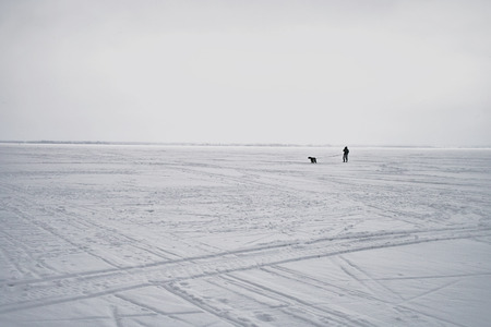 dog leash: Silhouettes of a man and his dog walking across a frozen lake, day time horizontal shot Stock Photo