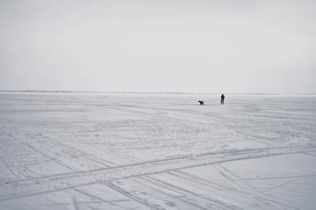 silueta hombre: Siluetas de un hombre y su perro caminando a trav�s de un lago congelado, tiro horizontal durante el d�a