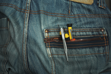 cropped out: Working tools sticking out of a rear jeans pocket, studio cropped shot