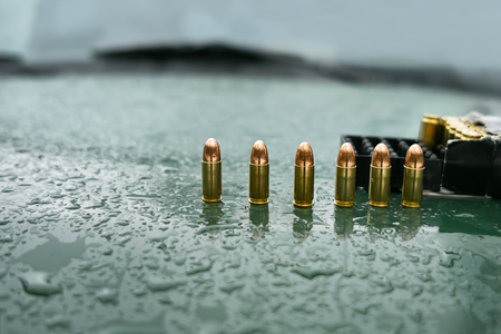pistol: Row of a pistol rounds and ammo box on a wet car hood, selective focus outdoor shot