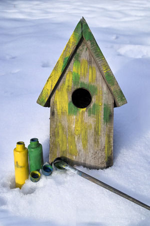 awaiting: Spring awaiting - fresh painted  wooden nesting box laid on a snow next to paintbrushes, vertical outdoor shot