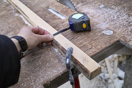 circular saw: Hand of a carpenter with measure tape next to a circular saw, selective focus shot with no people Stock Photo