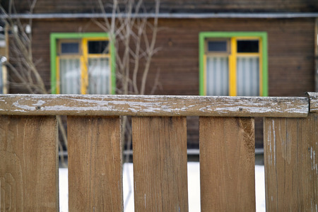 focus on the foreground: Old house looks abandoned behind a wooden fence, concept of privacy. Focus in the foreground