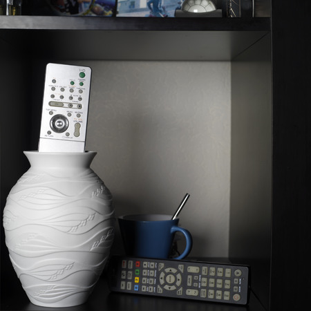 remote controls: TV remote controls laid on a black shelf next to white vase and blue tea cup, concept of free time, indoor square shot