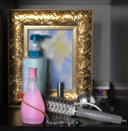 Hair brush and body care lotions next to a gold plated picture frame in ladies bedroom, cropped closeup shot