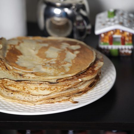 lofty: Closeup of the plate-sized buttermilk lofty pancakes with tea pot in the blurred background Stock Photo