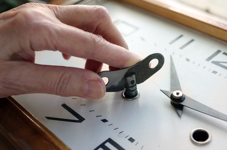 winding up: Female hand winding up a table clock looking retro, cropped closeup shot, concept of time Stock Photo