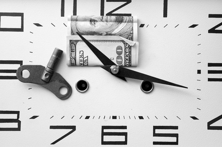 us dollars: Overhead shot of US dollars banknote placed under a clock hand, business metaphor, in black and white