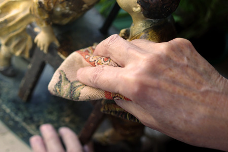 spotless: Cropped shot of a houseproud woman hand wiping dust off a looking antique statuette, shallow depth of field