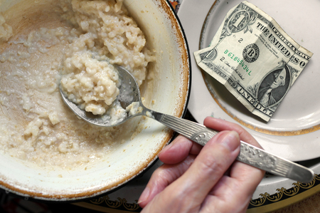 social issues: Hand with spoon and bowl with porridge next to a dollar bill, overhead shot, concept of poverty and social issues