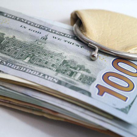 us sizes: Bundle of US dollars banknotes sticking out of a small wallet, still-life with selective focus
