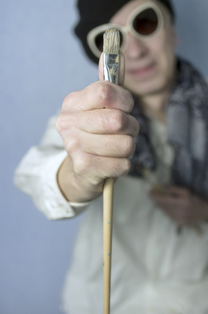 proportions of man: An artist holding a paintbrush in his hand, using it for measuring proportions, vertical shot with selective focus,