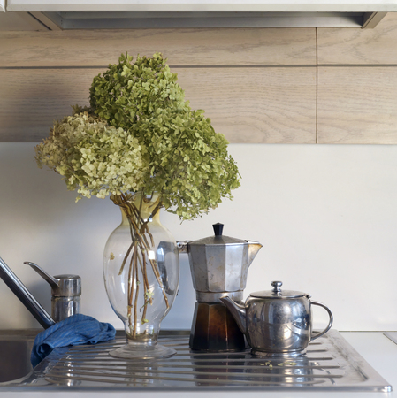 interior shot: Flowers in a vase next to the tea pot and coffee maker, square interior shot Stock Photo