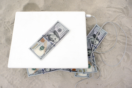us dollars: Overhead shot of a laptop and US dollars spread out around, day time shot with no people Stock Photo