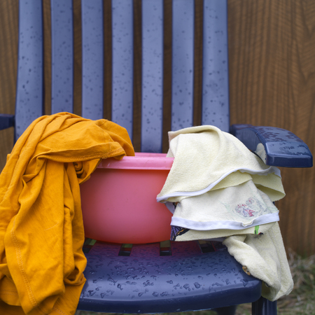washbowl: Various laundry in a pink washbowl, standing on the plastic chair, outdoor cropped shot