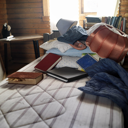 abandoned room: Books, lamp and garments scattered on the unmade bed in a looking abandoned room, contra light indoor shot Stock Photo