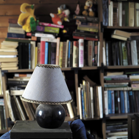 selective focus: Lamp in focus and books in mess on the wooden bookshelves in the blurred background. Indoor square shot