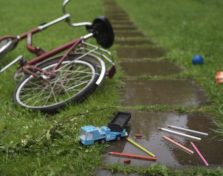 niños abandonados: Juguetes de niños, lápices, tiza y la bicicleta parece abandonados en la acera mojada. tiro al aire libre con el foco en el primer plano