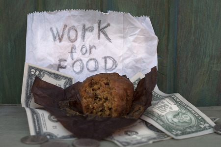 spread around: Bitten donut wrapped in paper and US dollars spread around next to a written message. Concept of employment issues